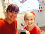 Lily showing medal for playing piano in talent show. Well done.